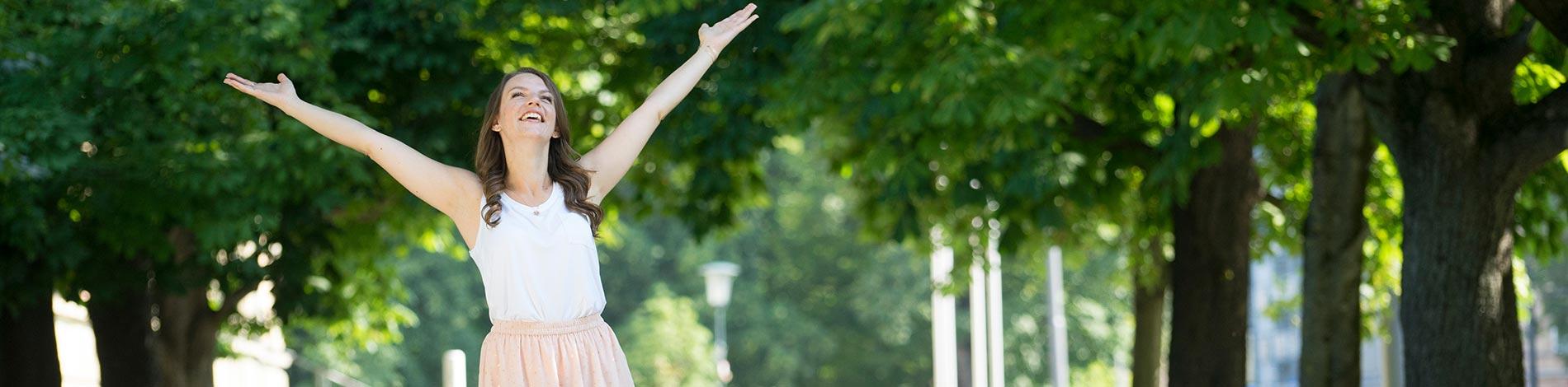 Frau nstrahlt in den Himmel und hebt ihre Arme