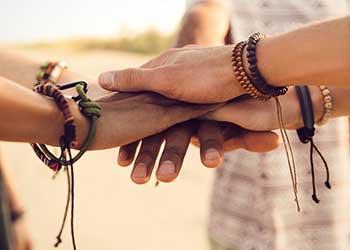 Menschen legen ihre Hände übereinander