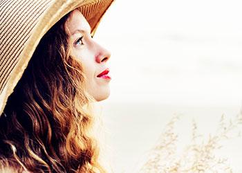 Frau mit Hut schaut verträumt in den Himmel